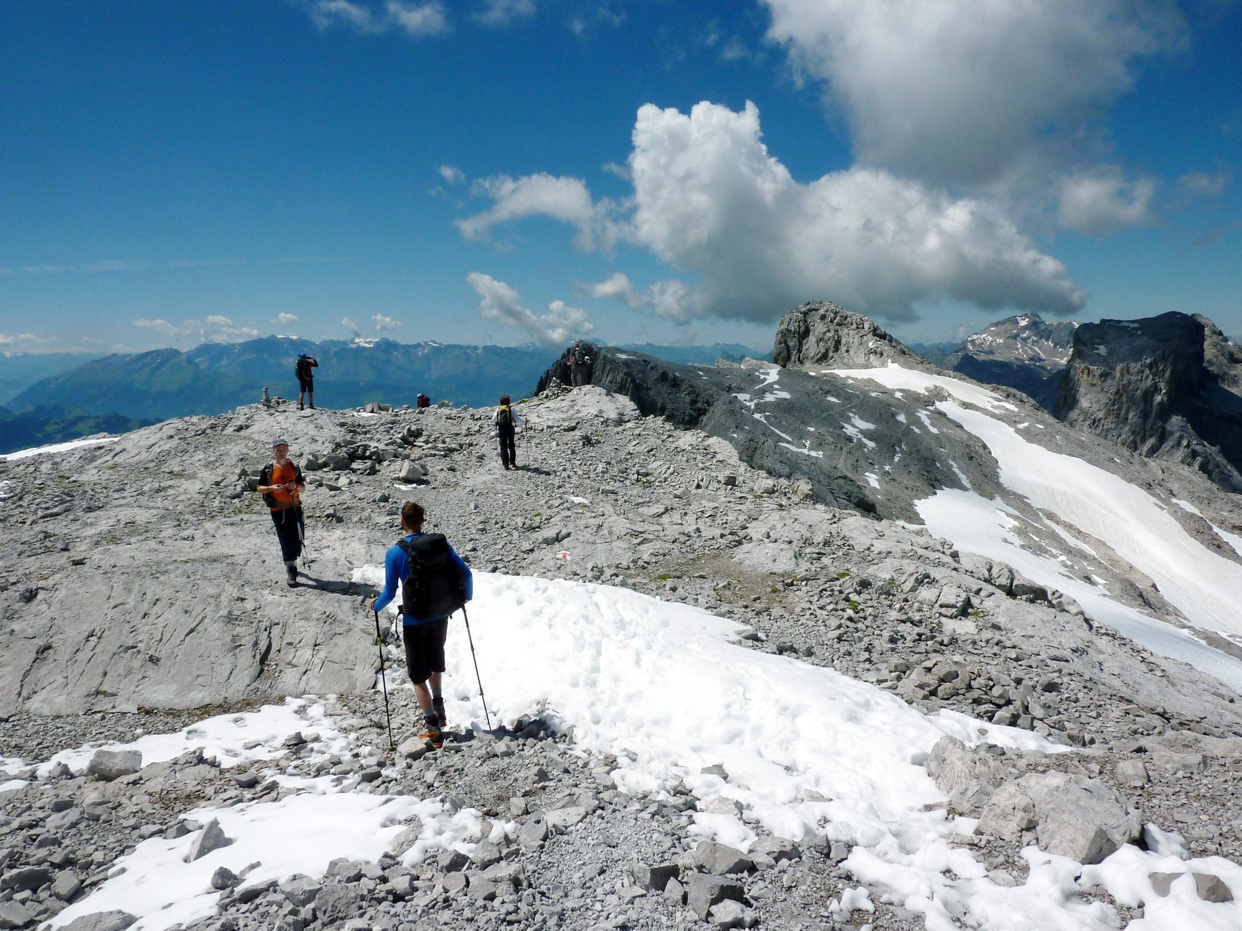 Reiseteilnehmer haben einen Gipfel erreicht und genießen den Ausblick